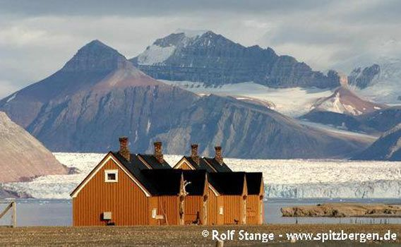 Houses in Ny Ålesund in front of the impressive mountain- and glacier-scenery of the inner Kongsfjord