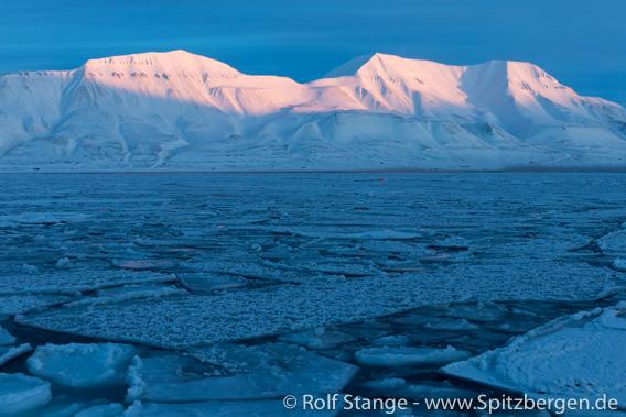 Eis im Adventfjord und Sonne auf den Bergen